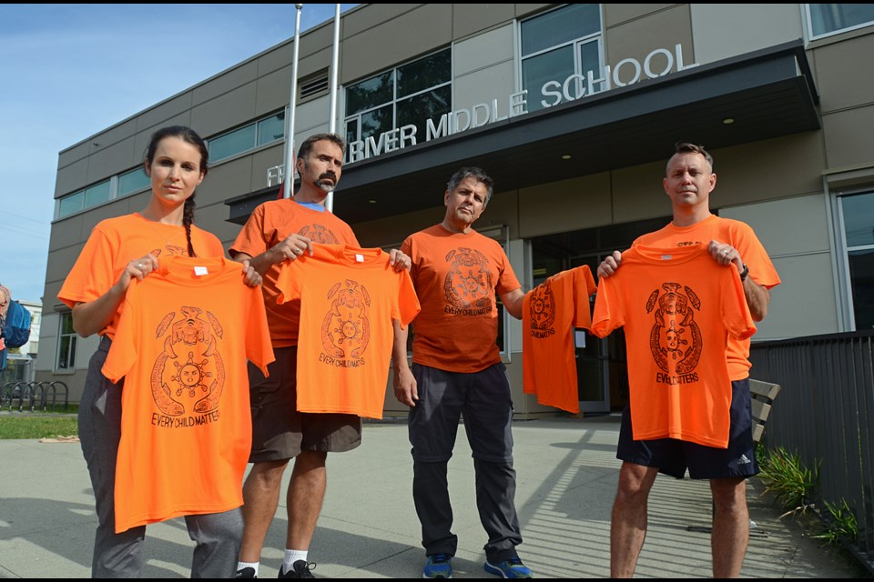 Principal Jen Harrison, teacher Christian Gibson, aboriginal support worker Lee Laufer and vice-principal Gary Pattern model the orange shirts featuring a winning design by Fraser River Middle School student Nicola Garcia.