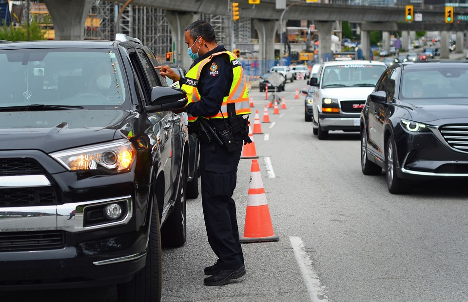 An Integrated Road Safety Unit officer pulls over a motorist during a traffic enforcement blitz on Lougheed Highway in Burnaby Monday.