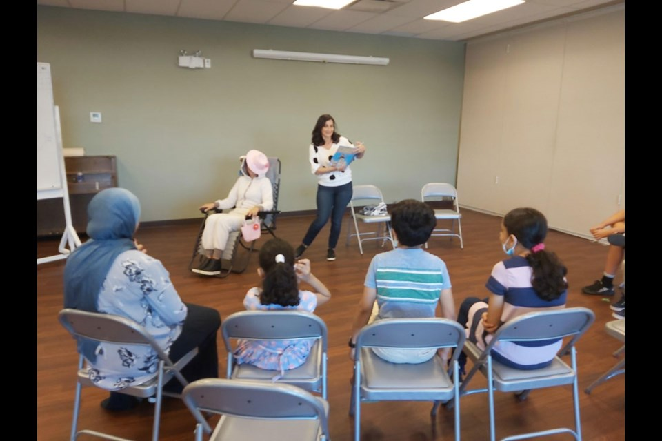 Rania Issa, Facilitator at Burnaby Neighbourhood House, running a book reading session for families at the South House.