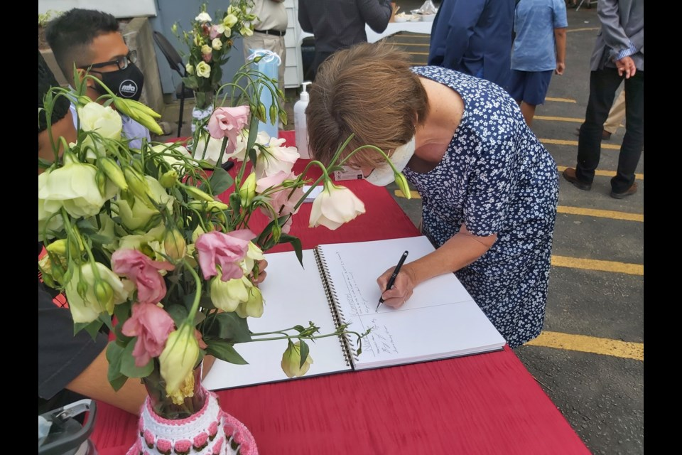 A Cambridge resident signs the guestbook at the Baitul Kareem Mosque open house held Thursday.