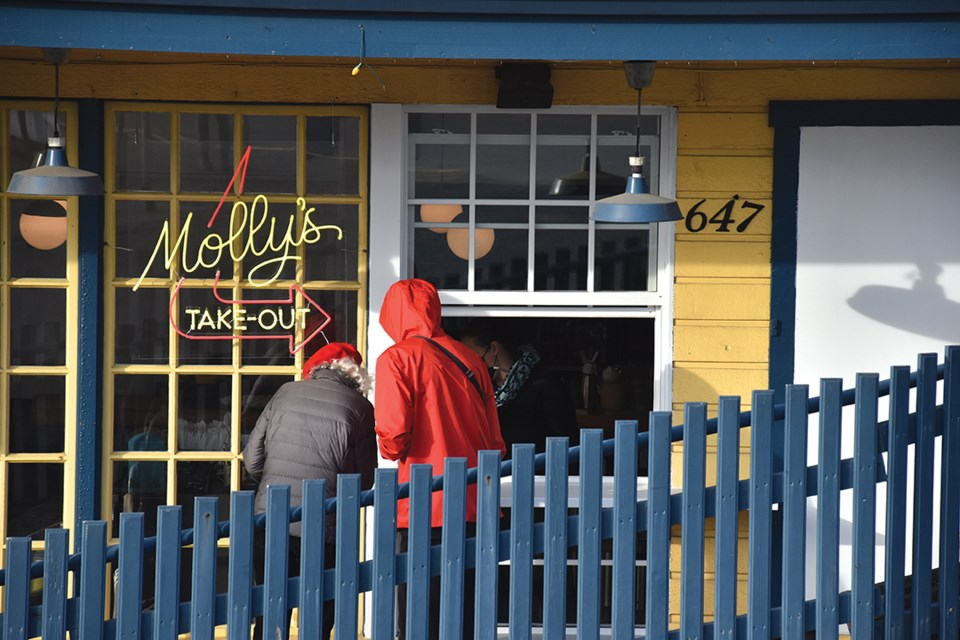 Diners order from the freshly installed takeout window at Molly's Reach restaurant in Gibsons on March 31, the day rules banning indoor dining at pubs, bars and restaurants came into effect in B.C.