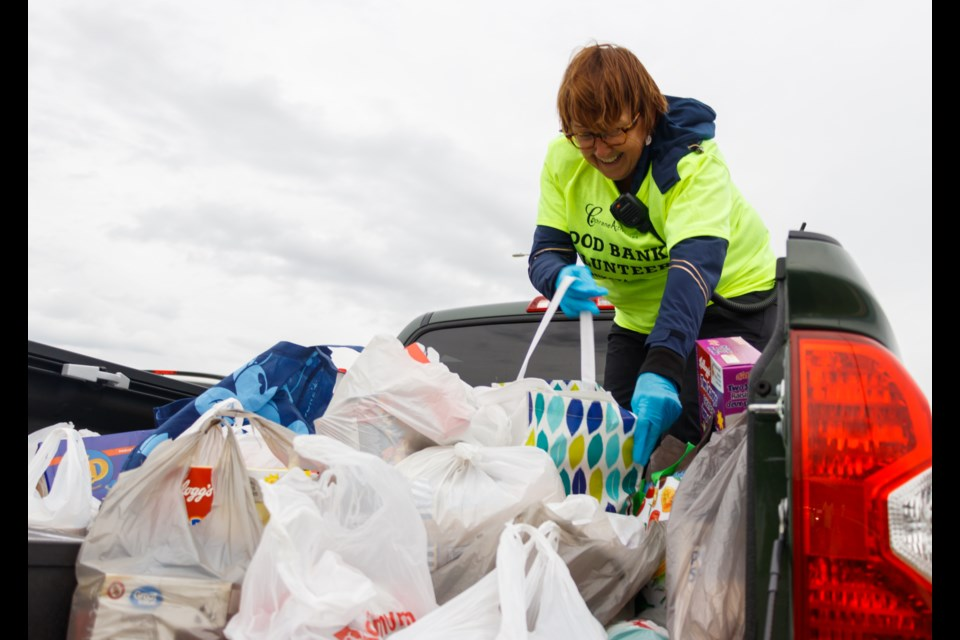 """Cochrane Activette Marcia Gilbertson collects food at the """"Movie Under the Stars"""" event at the Spray Lake Sawmills Family Sports Centre parking lot on Saturday (June 6). (Chelsea Kemp/The Cochrane Eagle)"""