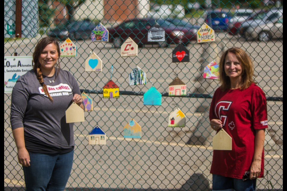 Cochrane High School educators Jasmyne Hazelwanter, left, and Lauraine Laudel show off painted tiny houses that are part of the Hope for Home project Thursday (June 25). (Chelsea Kemp/The Cochrane Eagle)
