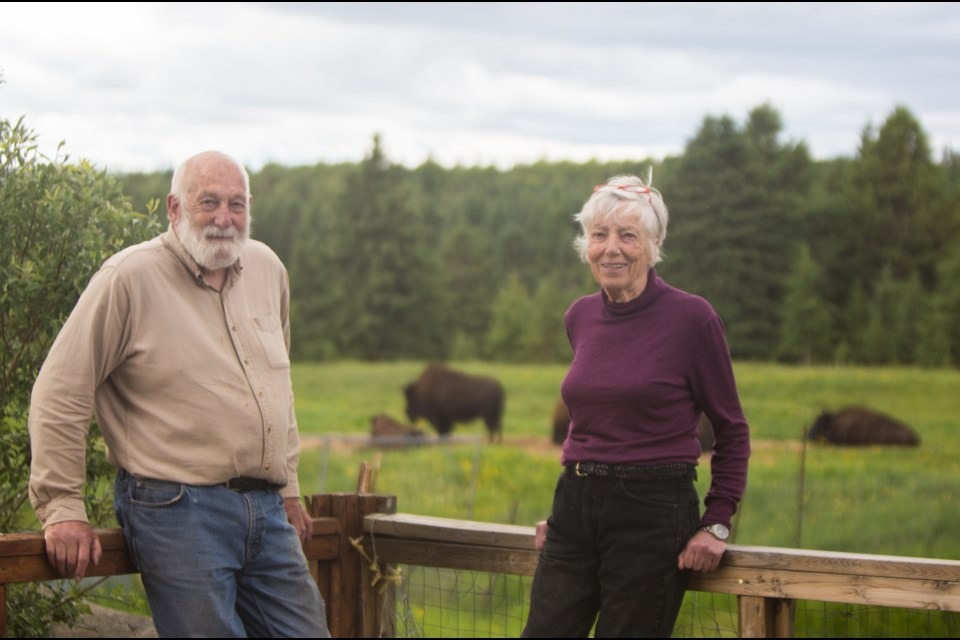 Cochrane Ecological Institute director Ken Weagle, left, and president Clio Smeeton stand in front of their buffalo hold on Saturday (June 27). (Chelsea Kemp/The Cochrane Eagle)