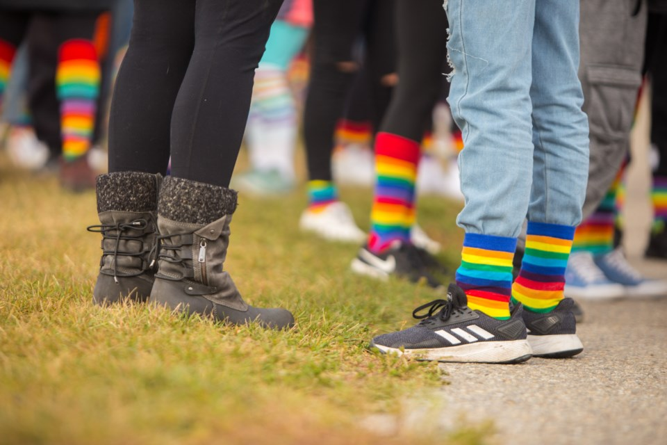 Cochranites walk a student who was bullied for wearing rainbow socks home during the Rainbow Sock Walk on Tuesday (Oct. 13). (Chelsea Kemp/The Cochrane Eagle)