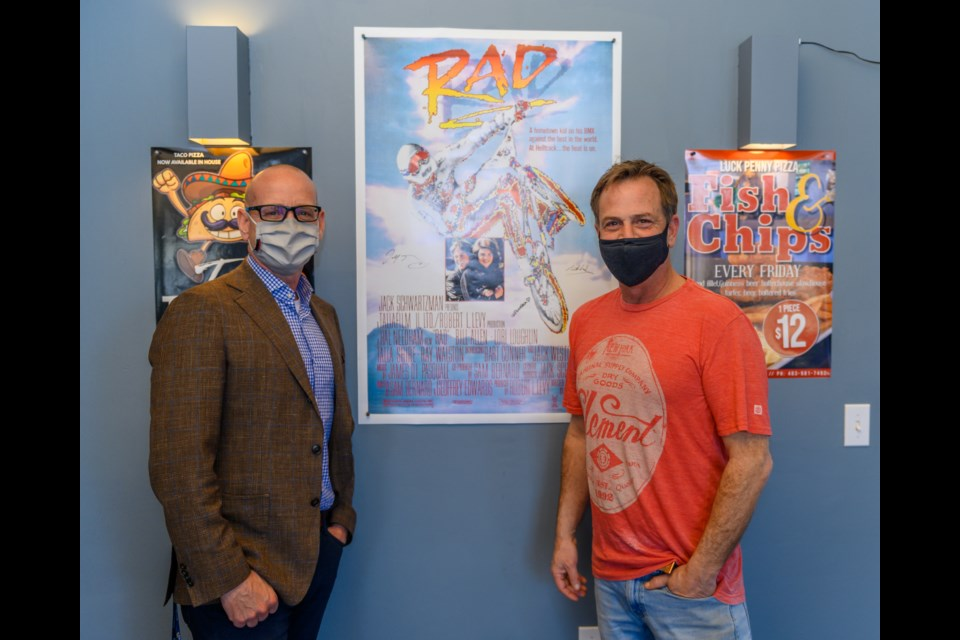 Mayor Jeff Genung and Tim Hall of Lucky Penny Pizza pose for their photo beside the signed poster for the movie RAD at Lucky Penny Pizza in Cochrane on Tuesday (April 13). (Photo by Jack Carter/The Cochrane Eagle)