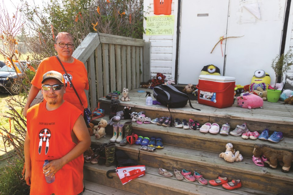 Eve Powder and Clement Holloway lead a march honouring children found in unmarked graves at former Residential Schools on Thursday (July 1). The walk began at the Chiniki Gas Station in Stoney Nakoda First Nation and ended at the Morley United Church. (Chelsea Kemp/The Cochrane Eagle)