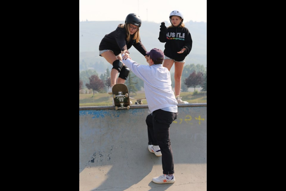 Shredz Skate Shop Sam Stuart helps 12-year-old Jayden drop in on a quarter pipe. (Tyler Klinkhammer/The Cochrane Eagle)