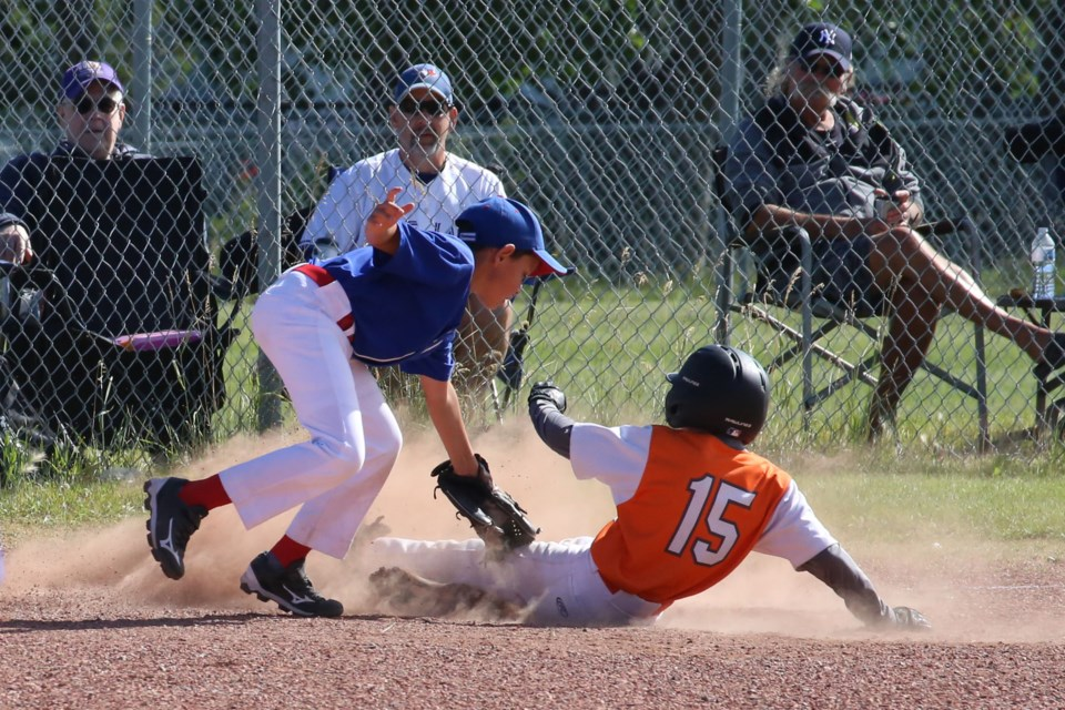 Ty Krooshoop connected on a hit and rounded the bases, sliding safely into third base. He would make it home on the next hit when his teammate, Braeden Bohach-Murray sent another ball into the outfield. (Tyler Klinkhamer/The Cochrane Eagle)