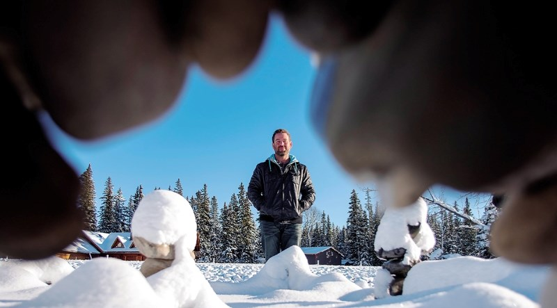 """Calgarian Luke Materi is framed by one of the structures he's building in his """";Winterfell""""project along the Elbow River in Bragg Creek."""