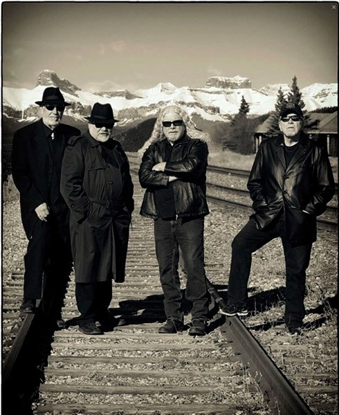 From left, John White, Barry Valgardson, Dave McRae, and Brian Burrows pose in front of the majestic Rockies.