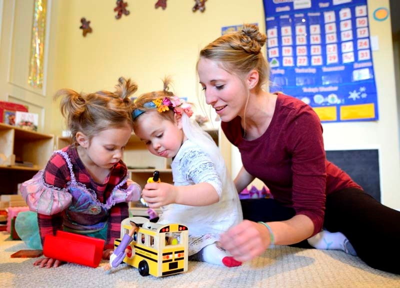 Childcare professional Jessica Walker plays with Siena Reade and Autumn Braaten during play time.