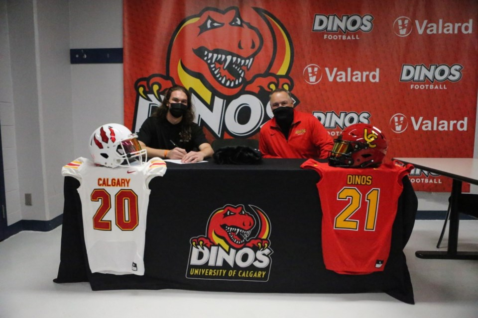 Jacob Mate signs his commitment letter alongside Dinos head coach Wayne Harris at the University of Calgary campus on Oct. 26. Photo submitted.
