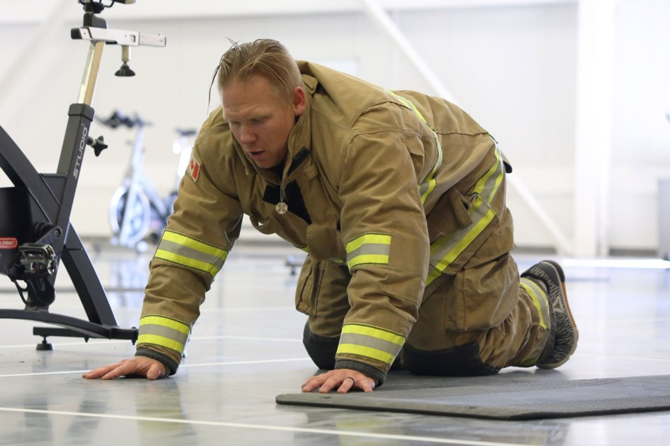 Jeremie Huolt, the founder of the 9/11 memorial workout, pauses for a breath between sets of pushups. Huolt said at the start of the event to remember the purpose of the workout. Every one of the 412 exercises performed was to honour one of the fallen emergency personnel who gave their life on 9/11. (Tyler Klinkhammer/The Cochrane Eagle).