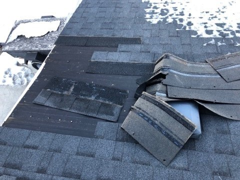 Shingles on a Cochrane resident's roof turned up by strong winds.