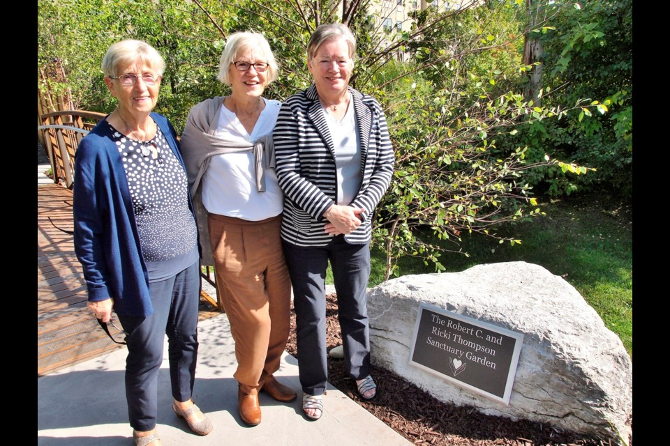 Ricki Thompson (far right) and her sisters Helen Blancke-Koops and Anne Lopes pose with the dedication plaque in The Robert C. and Ricki Thompson Sanctuary Garden at Campbell House in Collingwood. Photo courtesy of Dave West Photography