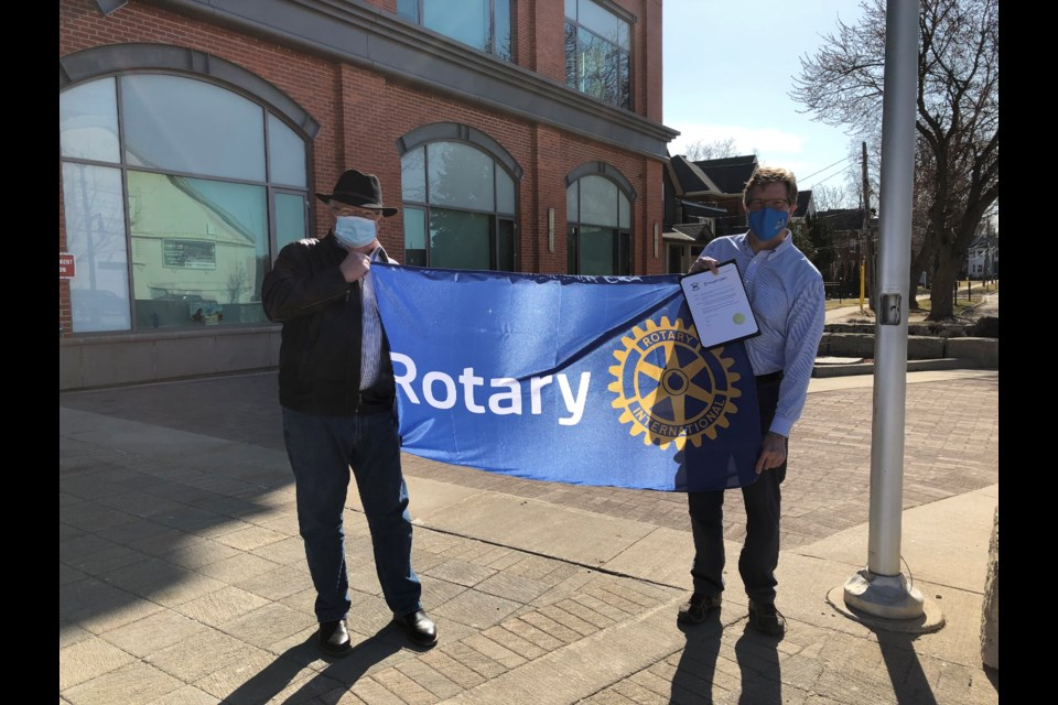 John Saul from the Rotary Club of Collingwood, South Georgian Bay with Collingwood Mayor Brian Saunderson as they raise the Rotary flag at the Collingwood Public Library.