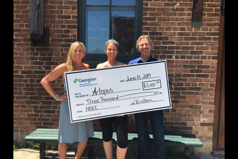 Laura Paige-Hamelin from Artopus (centre) receives first place honours and $3,000 from the Henry Bernick Entrepreneurship Centre (HBEC) in the recent exC!te Business Pitch Competition. She also won the technology prize sponsored by AdBank. HBEC's Programs and Partnership Manager Sara Bentham, and Don Bourne, HBEC Client Service Advisor and mentor, presented the prize.