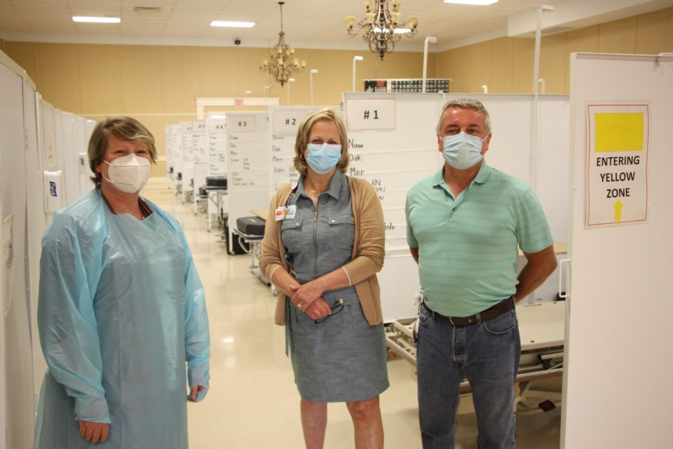 Aimee Stinson, nurse manager, Norah Holder, hospital CEO and present, and  John Widdis, manager of plant operations and maintenance for the hospital, stand in front of the new beds and cubicles at the Alternative Health Facility set up by Collingwood General and Marine Hospital. Erika Engel/CollingwoodToday