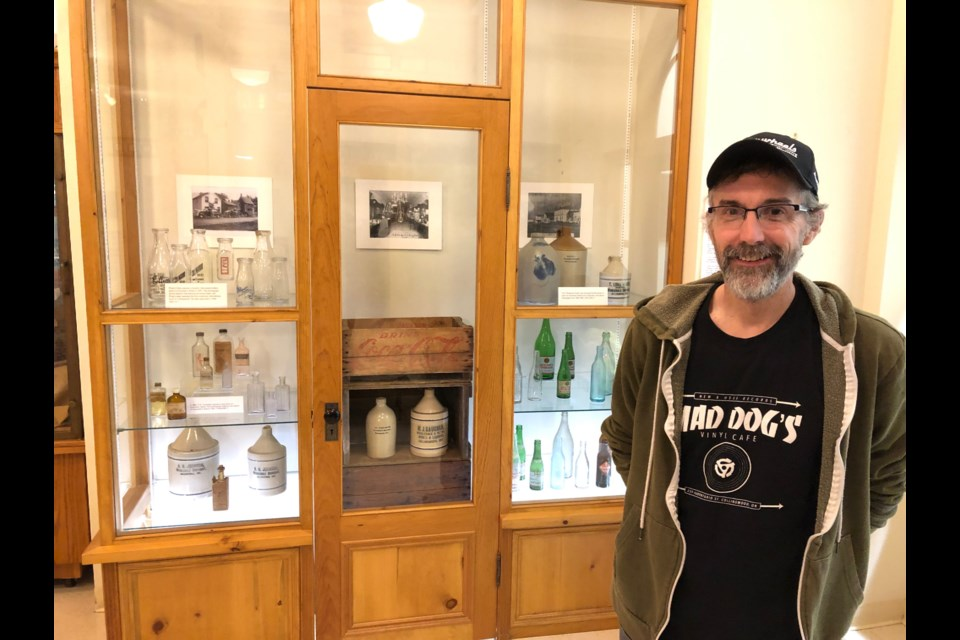 Sean Redman with his bottle collection displayed at the Collingwood Museum from now through February. Erika Engel/CollingwoodToday