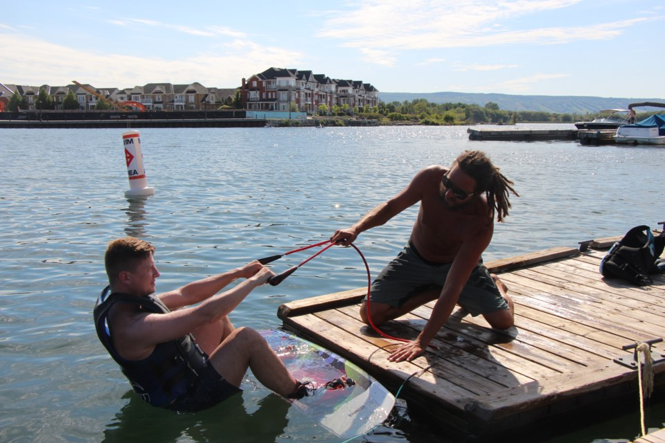 Chris Smith teaches a new wakeboarder how to get up out of the water while holding the cable. Maddie Johnson for CollingwoodToday