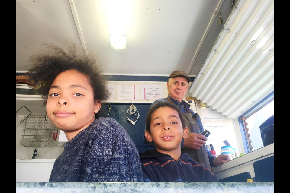 """Chantel, 10, and John, 8, help out Ivan sling the smoking street """"meet"""" at the DC Farmer's Market in downtown Dawson Creek. It goes until 2pm today!"""