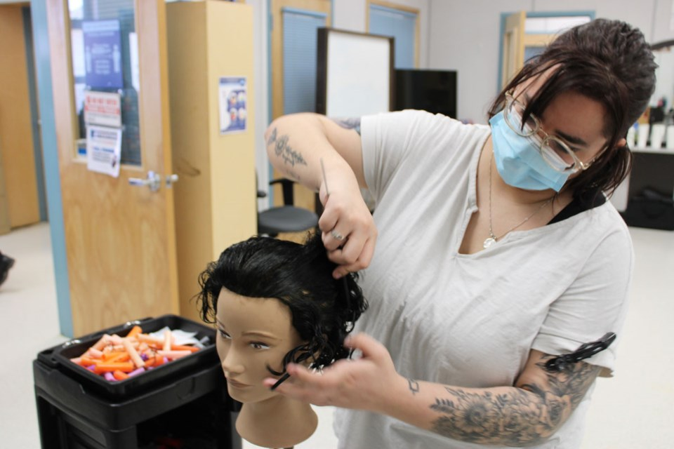 Student Savannah McEwen practices perming on a mannequin.