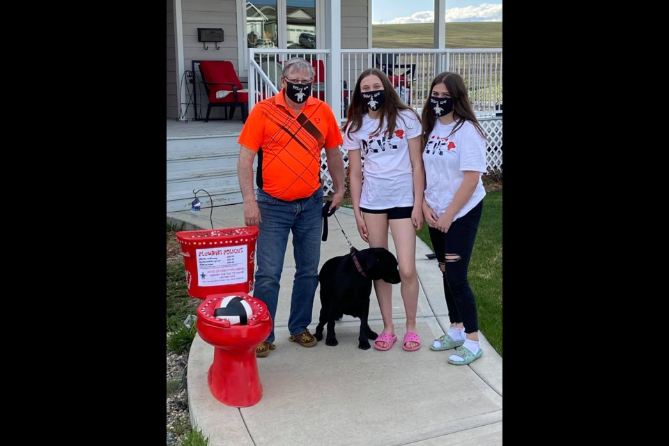 Members of the DCVC U15 team drop off the travelling toilet to Mayor Dale Bumstead's house on May 16, the first day of the team's fundraiser.