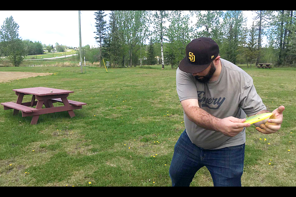 Dillon Giancola throws a drive during a round of disc golf at the course in Pouce Coupe Park.