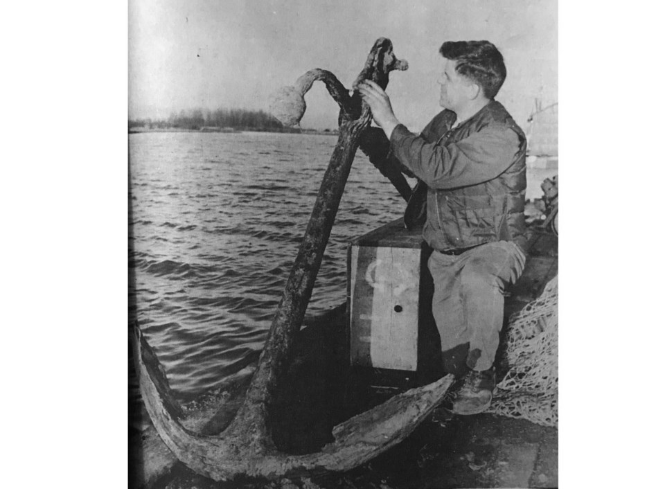 1969 photo of doug massey checking out a century-old anchor discovered