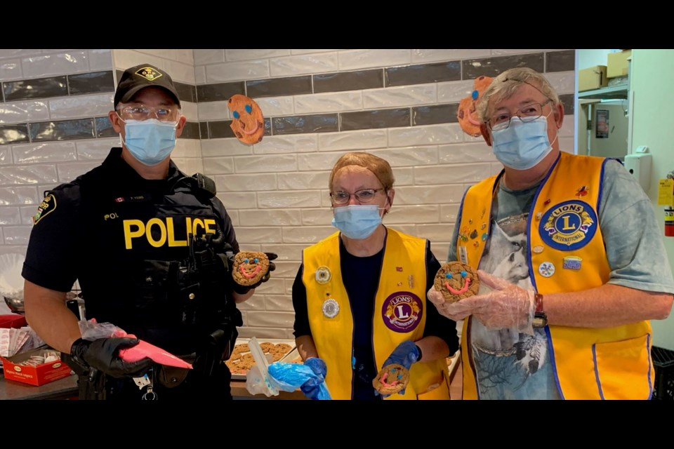 Elliot Lake OPP Constable Phil community safety officer assisted local Lions Club members with decorating the cookies. Also helping out were Club President Roger Collett and First Vice President Russell Foy and Constable Phil Young and Lions Members Linda Collett and Leo Deveu.