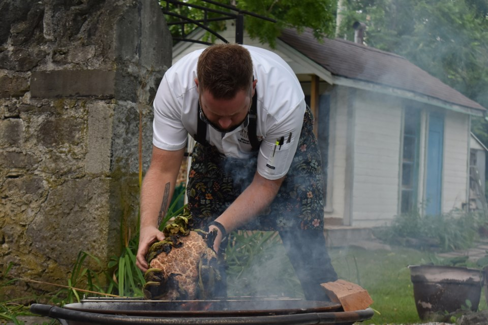 Chef Arron Carley cooks a cauliflower on an outdoor firepit to prepare a vegetarian dish.