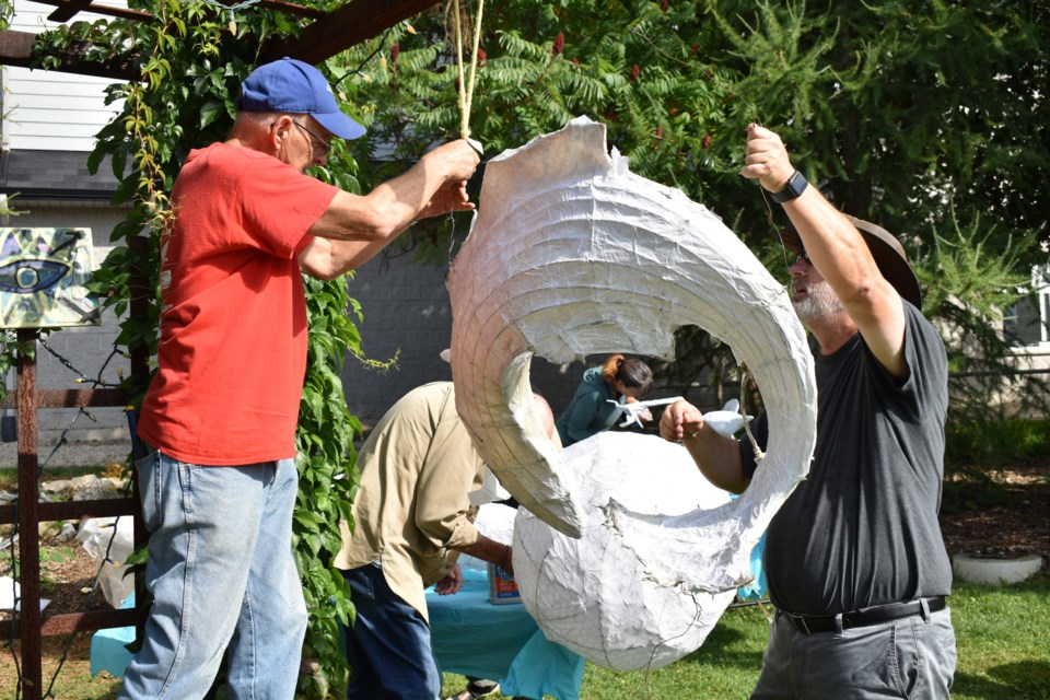 Dick Harmon, left, and Andrew Pipe jointly hang one of the sculptures so volunteers can tackle them from both sides.