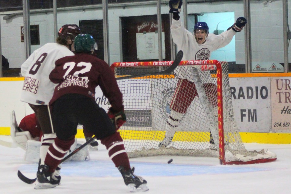 Team White's Nathan Gagne and Jeremi Tremblay (right, behind net) celebrate Gagne's goal in Bombers' maroon and white game Sept. 4.