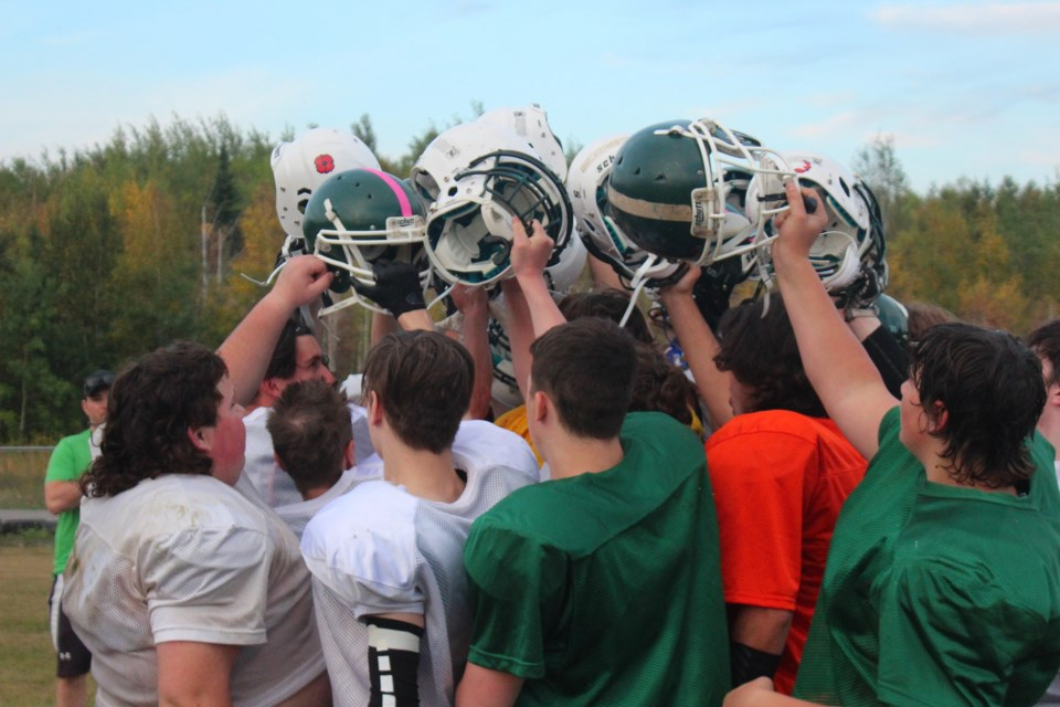 Players hoist their helmets together at the end of practice.