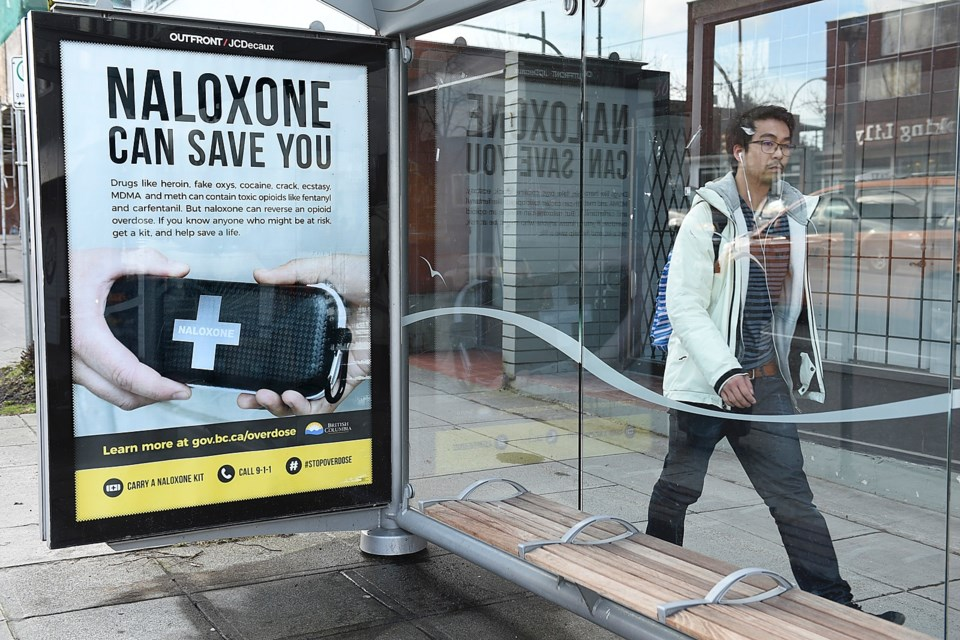 A man walks past a Vancouver bus shelter with a poster promoting naloxone kits. Photo Dan Toulgoet