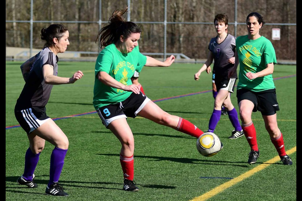 Poised and ready, the New Westminster Rush's Leni Burton, at left, and teammate Emily McLeod, in background, look to time their move against a Richmond Breakers ball carrier last week in the Metro Women's Soccer League Classics Div. 2 cup final.