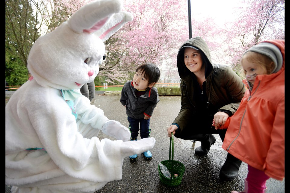 Three-year-old Ariel Jang peers at the Easter bunny during the Hillview Preschool Easter event on April 8.