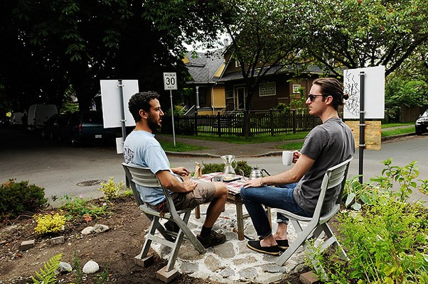 George Rahi (left) and Julien Thomas enjoy a cup of coffee on the traffic calming circle at St. George and 10th Ave.