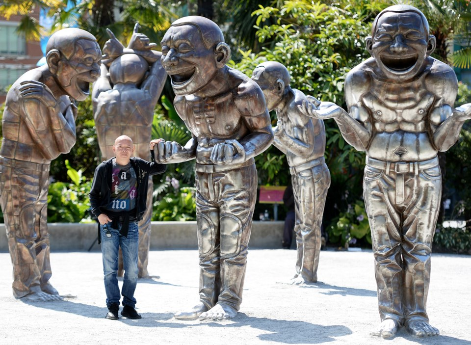 A-maze-ing Laughter, is made up of 14 giant smiling bronze men, all featuring artist Yue Minjun's sm