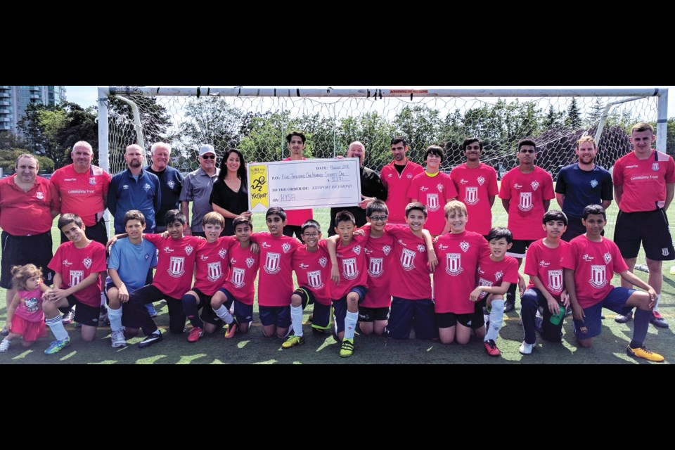 Richmond FC chair Rein Weber, staff and players presented a cheque for $5,171 to Richmond KidSport chapter on Monday, representing donations for this week's camp at Minoru Park being run by Stoke City FC coaches. Accepting the donation is Richmond Kidsport chair Bob Jackson and director Alexa Loo.
