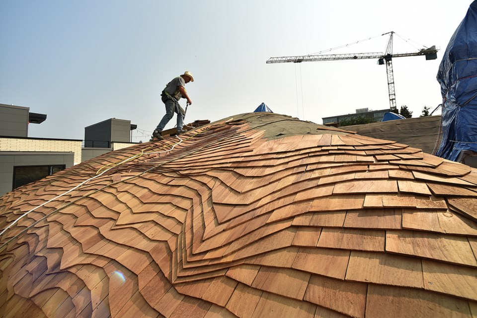 """The laborious task of re-roofing the so-called """"Hobbit house"""" on West King Edward Ave. is underway. Photo Dan Toulgoet"""