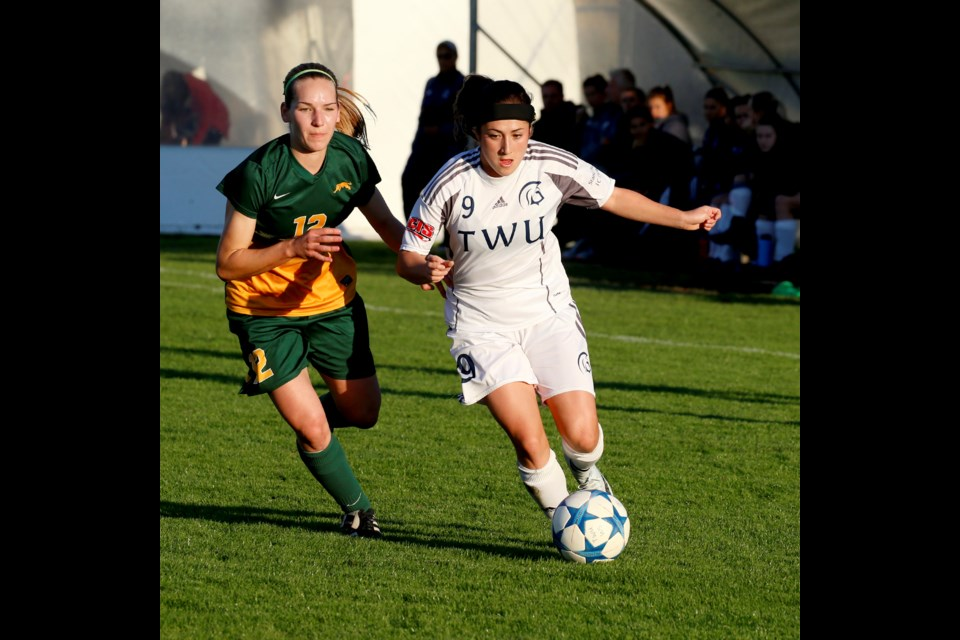 Burnaby native Seina Kashima, at right, moves the ball forward for the Trinity Western University Spartans last week. The fourth-year player will set a new Canada West career assist record with her next helper.