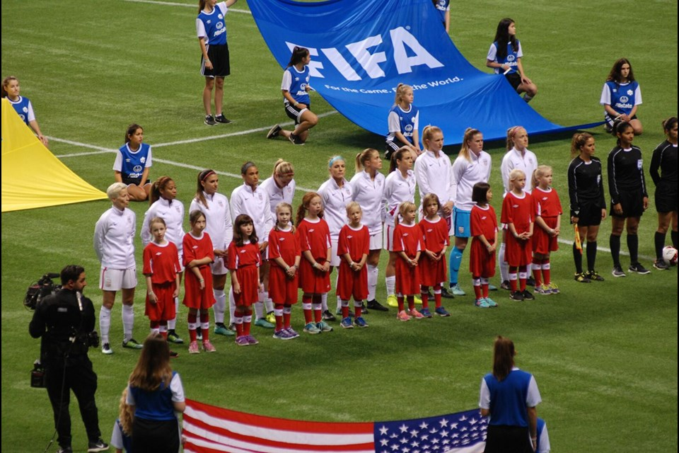 Standing for the Star Spangled Banner with members of the US National Women's Soccer Team.
