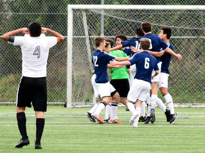 JENNIFER GAUTHIER PHOTOThe Dr. Charles Best Blue Devils celebrate their fifth senior boys' provincial soccer championship as Panorama Ridge's Ravjot Duhra walks off the pitch, Saturday at the Burnaby Lake Sports Complex. Best beat the Thunder 2-1 on a late penalty kick goal by striker Quinn Deslauniers.