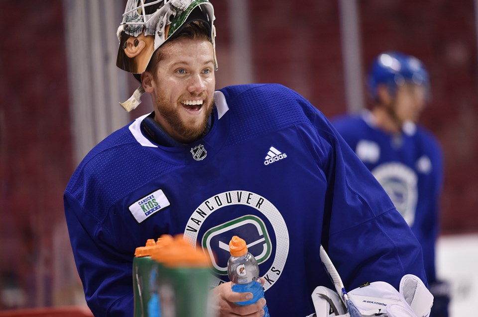 Jacob Markstrom enjoys a water break at the Canucks bench during practice.