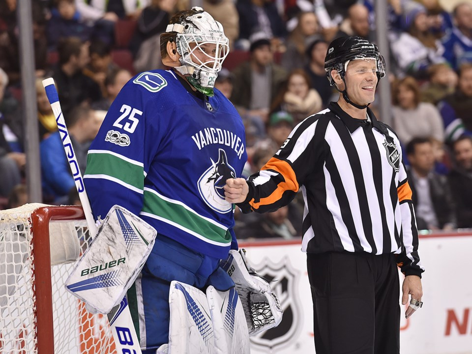 Jacob Markstrom shares a moment with a referee in the Canucks net.