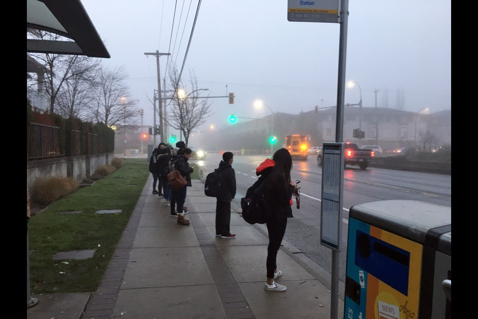Wait for it: Students wait at Howes Street and Ewen Avenue for the bus to 22nd Street SkyTrain station and then to New Westminster Secondary School. School board trustee Mary Lalji would like to see the school district offer a bus service for students who live in Queensborough and attend the high school.