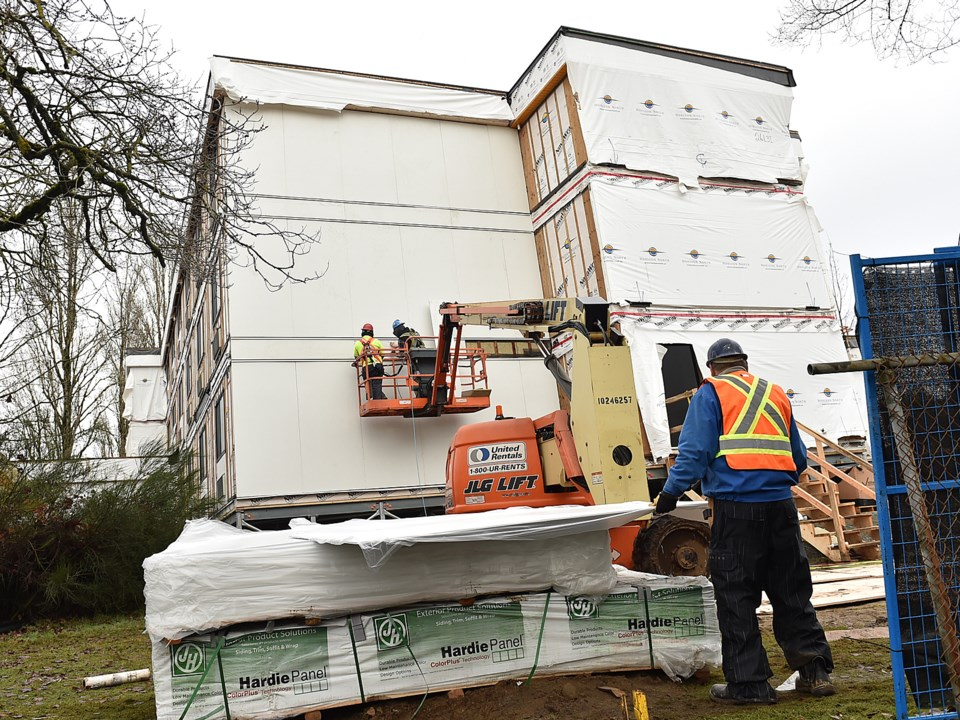 Construction crews were busy Monday assembling a 78-unit modular housing complex that will be home t