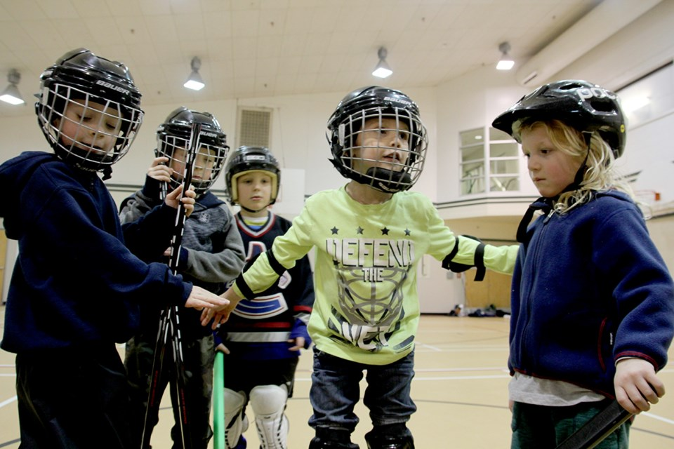 On the left, young hockey players crowd around coach Bristow in anticipation of their cheer. At right, Liam,